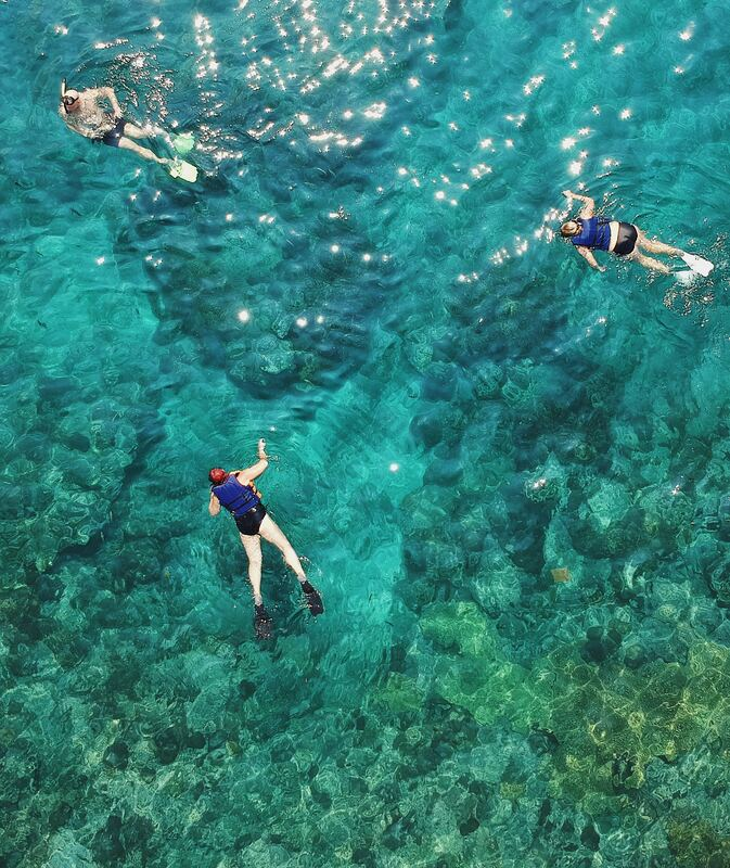 Three people snorkeling in the crystal clear waters of Gozo.Picture