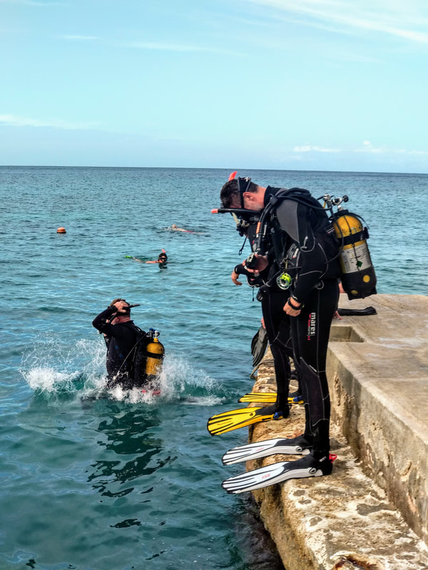 Photo of divers practicing their giant stride entry on and Open Water Course in Gozo..