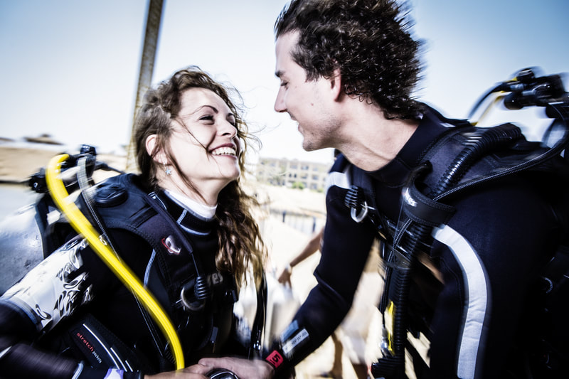 Photo of a couple looking at each other lovingly during their open water course.